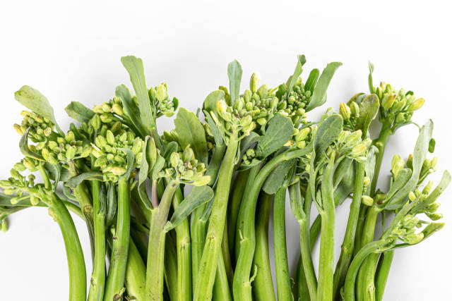 Fresh raw broccolini twigs on white, top view