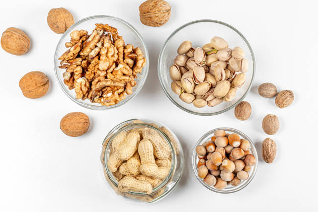 Background with different types of nuts in the skin and without