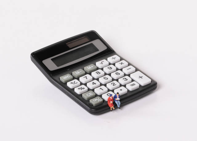 Couple sitting on calculator on white background