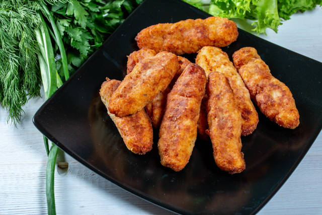 A lot of fish fingers on a black plate with greens in the background