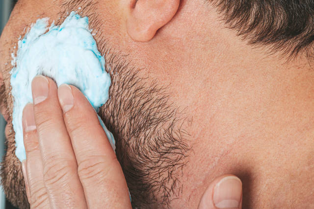 Portrait of male putting shaving foam on his beard. Skin care concept