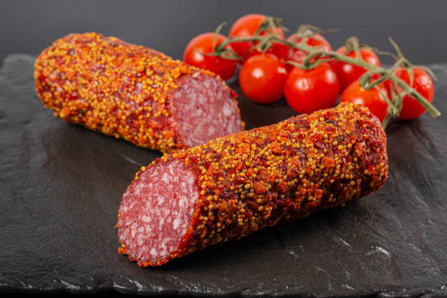 Smoked salami on black background with cherry tomatoes