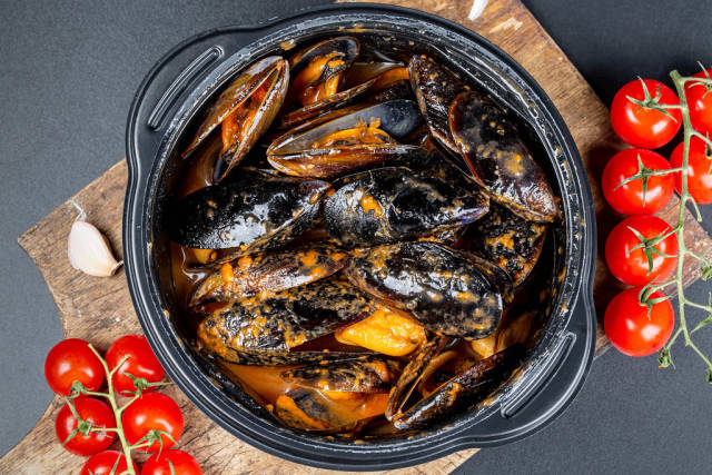 Top view, mussels with garlic and tomato sauce in a black pan