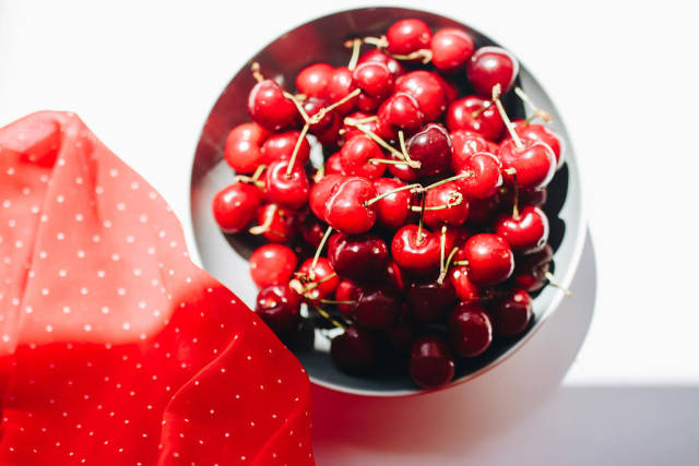 Top view of fresh cherries in a bowl with red fabric