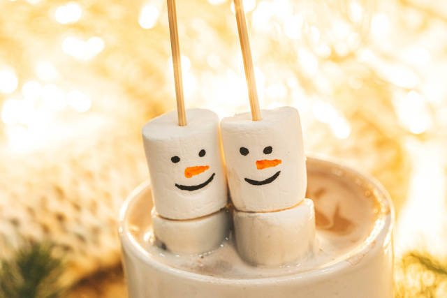 Snowmen made from marshmallows in a cup of hot coffee, close-up