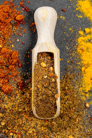 Top view wooden scoop with ground pepper mixture on spice background