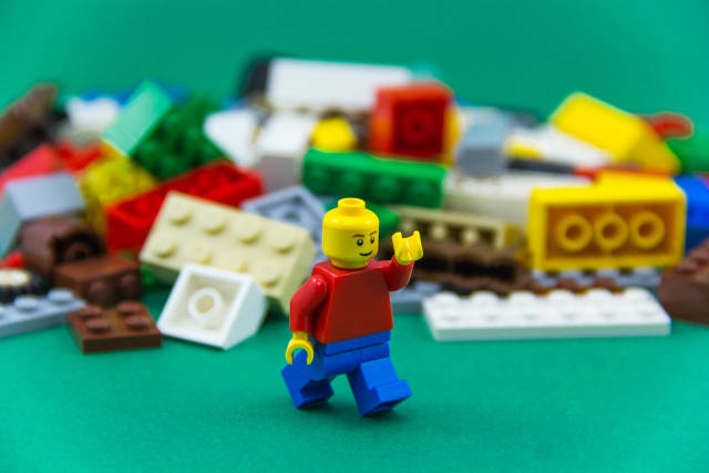 Lego Man running in front of Legos