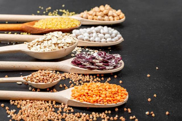 Various cereals and legumes in wooden spoons (Flip 2019)