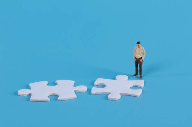 Miniature man looking at two jigsaw puzzle pieces