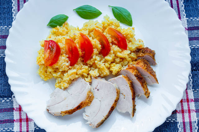Rice with chicken fillet, tomato slices and fresh Basil leaves