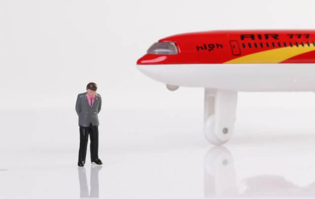 Sad businessman standing near airplane