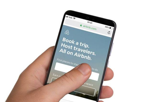 Male hands holding smartphone with an open Airbnb application