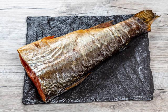 Headless smoked salmon on a black stone tray