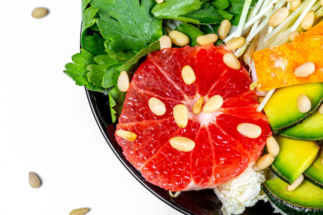 Close-up salad with grapefruit, avocado, micro greenery and pine nuts