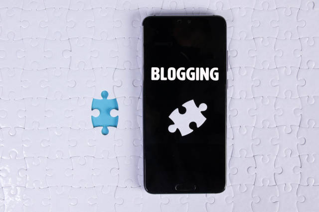 A modern big smartphone with a touch screen lies on a white jigsaw puzzle with Blogging text
