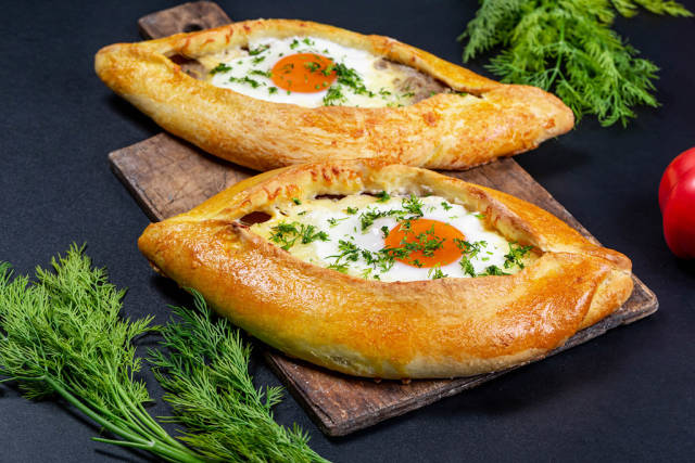 Delicious homemade Adjarian khachapuri on a dark background with green dill