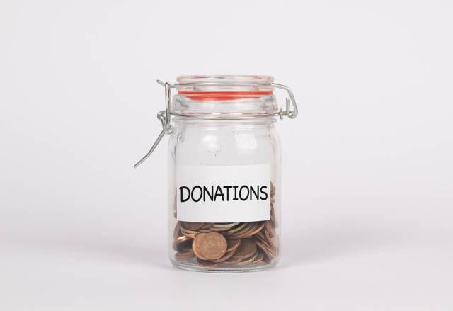 Einmachglas gefüllt mit Münzen und Zettel mit Wort DONATION (Spenden) vor weißem Hintergrund