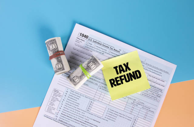 USA tax form 1040 for US individual tax return with money rolls and sticky note with Tax Refund text