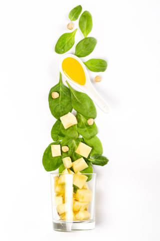 Top view of spinach leaves, honey, pineapple slices, hazelnuts and glass on white