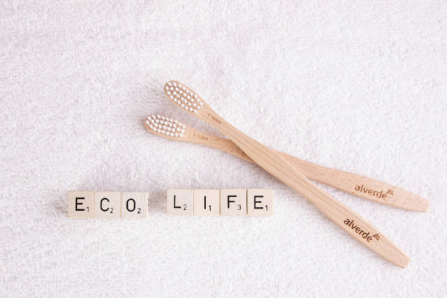 Wooden toothbrushes with eco life text on white towel