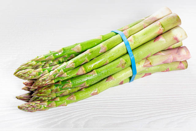 A bunch of fresh asparagus on a white wooden table