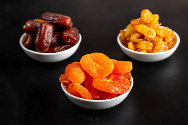 Dried apricots, raisins and dates in white masks on a black background