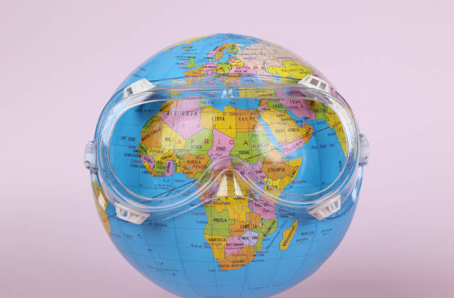 Globe wearing safety goggles