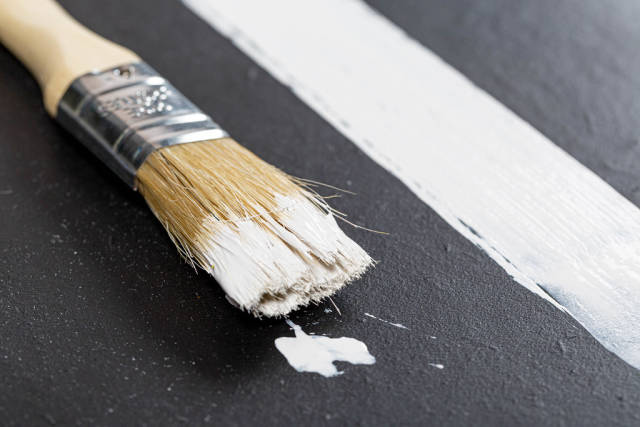 Brush and strip of white paint on black background