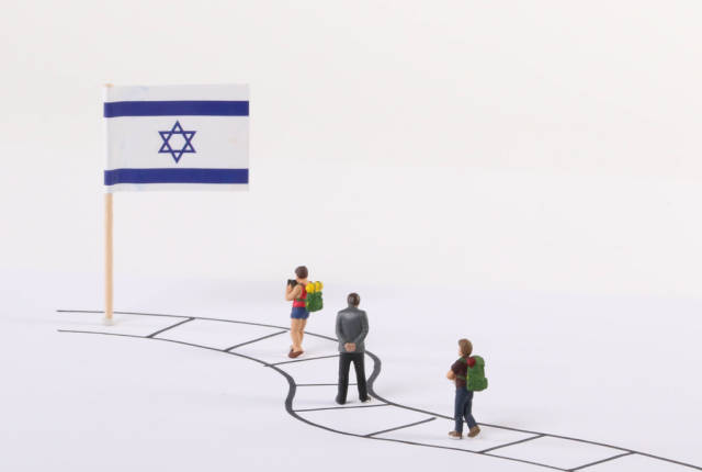 Miniature people walking on a path to the flag of Israel