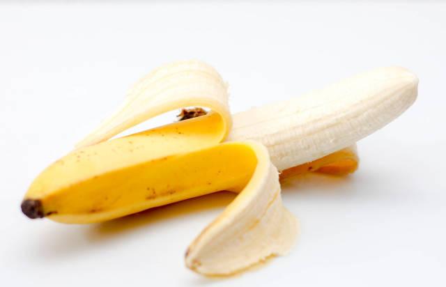 Geschälte Banane vor weißem Hintergrund