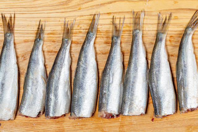 Top view raw fish sprats on the kitchen Board
