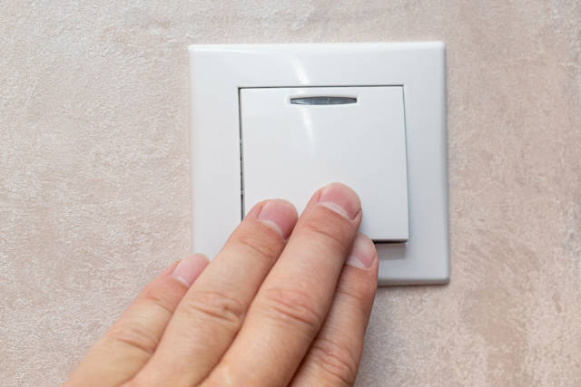 Mans hand with fingers on light switch, about to turn off the lights