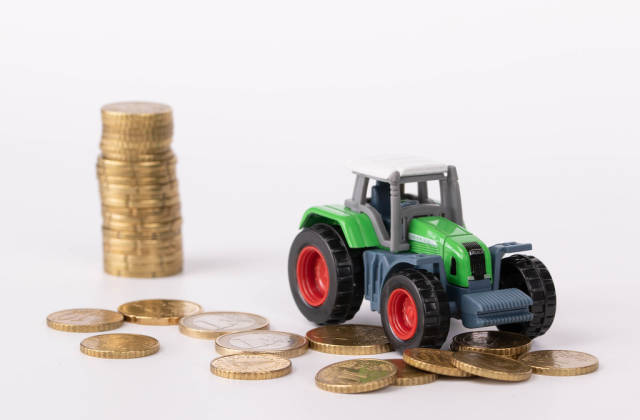 Green tractor with coins on white background