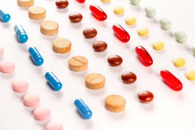Multi-colored capsules and tablets, medical background