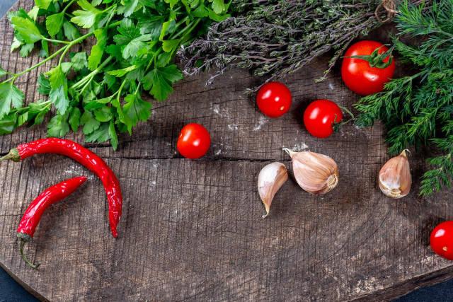 Paprika, Tomaten, Knoblauch und verschiedene Kräuter auf einem Holztisch