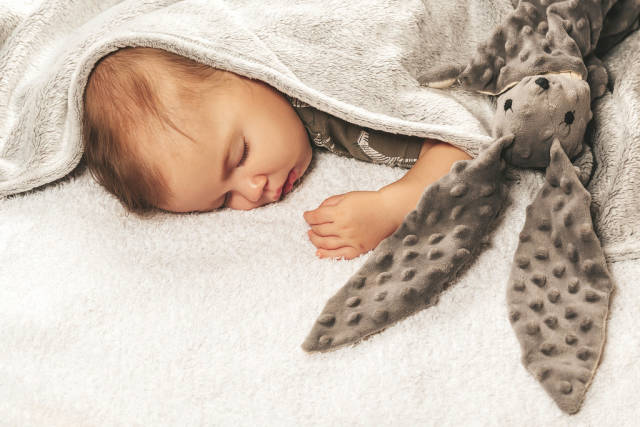 Sleeping baby on the bed covered with a blanket with a toy rabbit