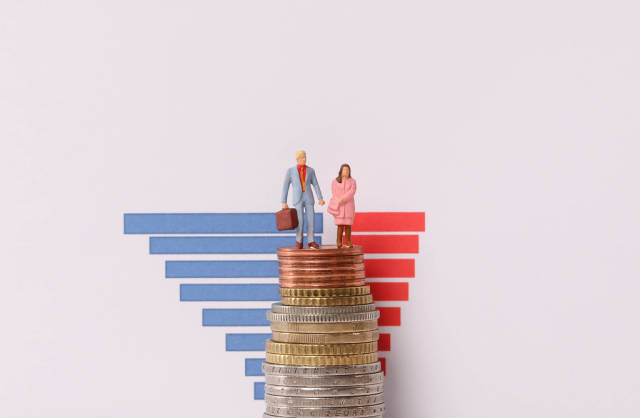 Man and woman standing on a stack of coins with bar graph