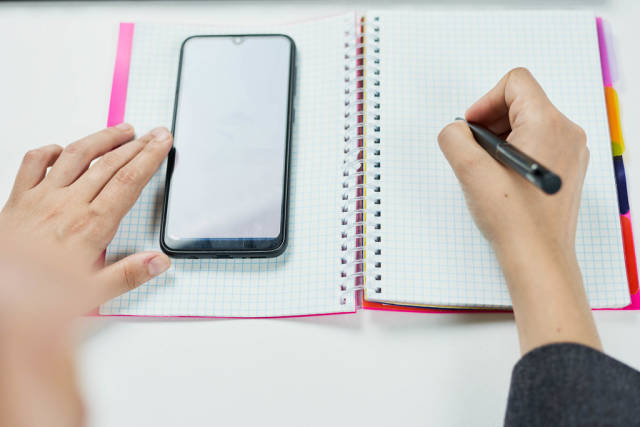Businesswoman checking calendar on her smartphone and writing notes on the notepad