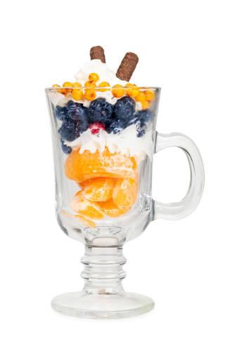 Glass mug with fruit dessert on white background