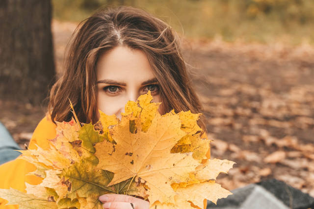 Close-up of a girls face and yellow leaves
