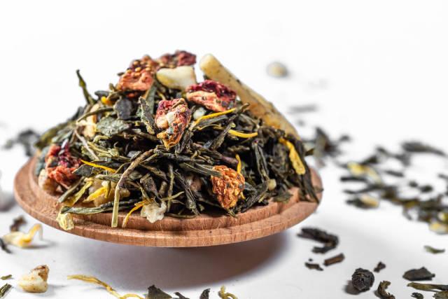 Nahaufnahme getrockneter Früchtetee aus Erdbeeren, Bananen und grünem Tee auf Holzlöffel