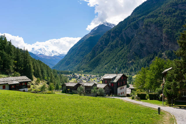 Path descending from mountains to a Swiss valley with a village
