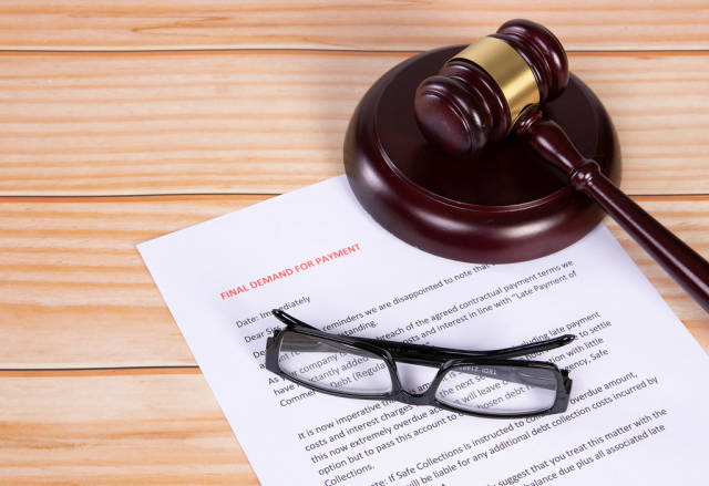 Final Demand for Payment document with glasses and a wooden judge gavel