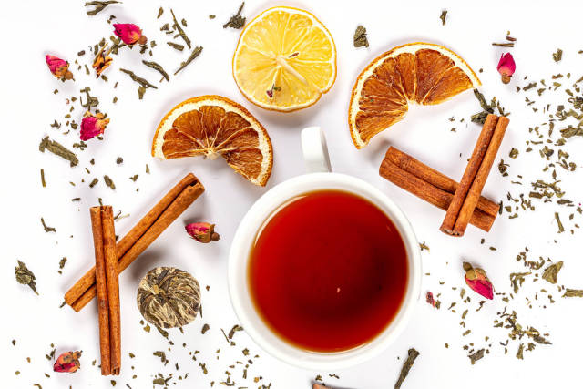 Top view, cup of tea on white background with cinnamon, dried lemons and flowers