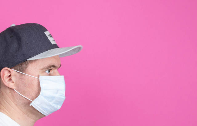 Young man with medical flu mask