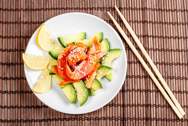 Top view, diet salad with smoked salmon, avocado and sesame seeds