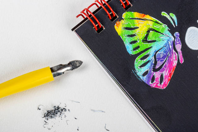 Notepad with a multicolored butterfly drawn and a stichel pen on a white background. Grattage drawing