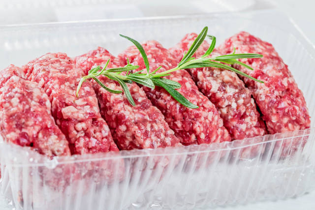 Raw minced meat for cutlets and rosemary branch