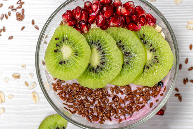 Oatmeal with flax seeds, kiwi slices and pomegranate. The concept of a healthy Breakfast. Top view
