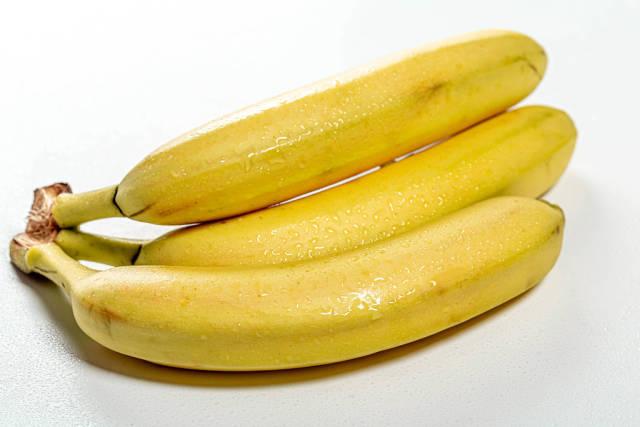 Three fresh ripe bananas with drops of water